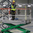 warehouse sign installers on lifts