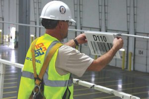 installing overhead warehouse barcode sign
