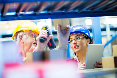 Warehouse workers with barcode scanner checking inventory