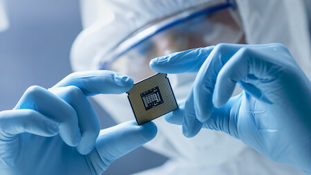 Engineer in sterile cleanroom holding microchip
