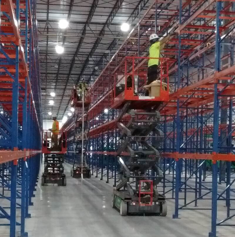 Warehouse label installation crew on scissor lifts