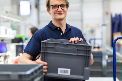 warehouse worker with barcoded plastic bin